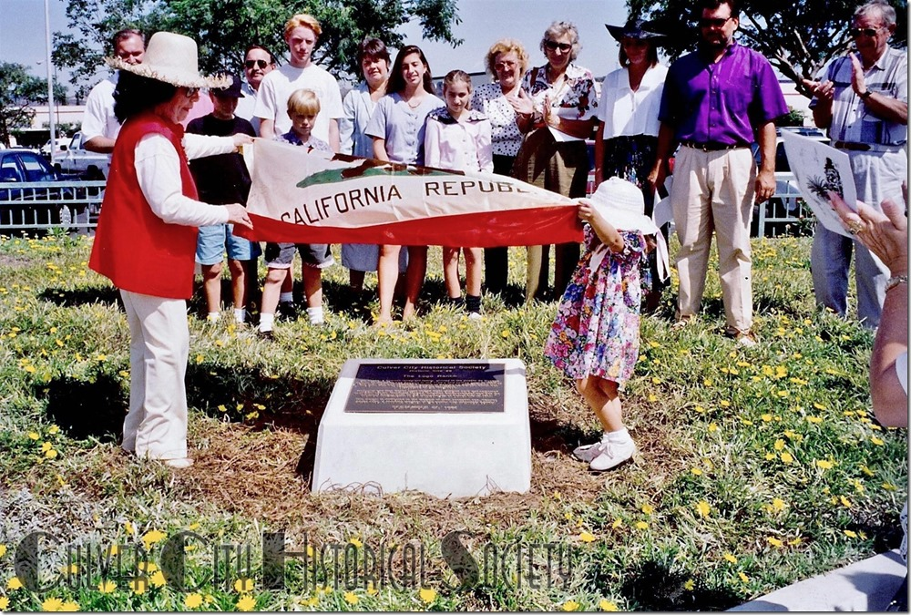 Society Madrina (godmother), Clarita Marquez Young, who took the lead in the marking of historic sites, gets help to unveil a marker.