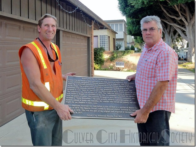 Historic Site #13 marker in the hands of city employees Mike Machado and Carlos Lugo