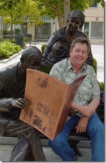 "Chris Wilde next to a ""A Moment in Time,"" a public art piece in front of the Culver Hotel depicting Harry Culver, his wife Lillian, and their baby Patricia, who would become Wilde's mother."