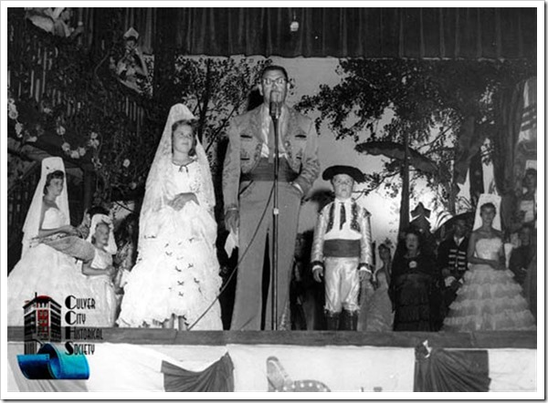 Fiesta photo in the mid 1950s, on the Veterans Memorial Building stage. Fiesta court in the background. Charles R. Lugo in one of Cesar Romero's costumes on loan from MGM at microphone, flanked by his children. - Culver City Historical Society